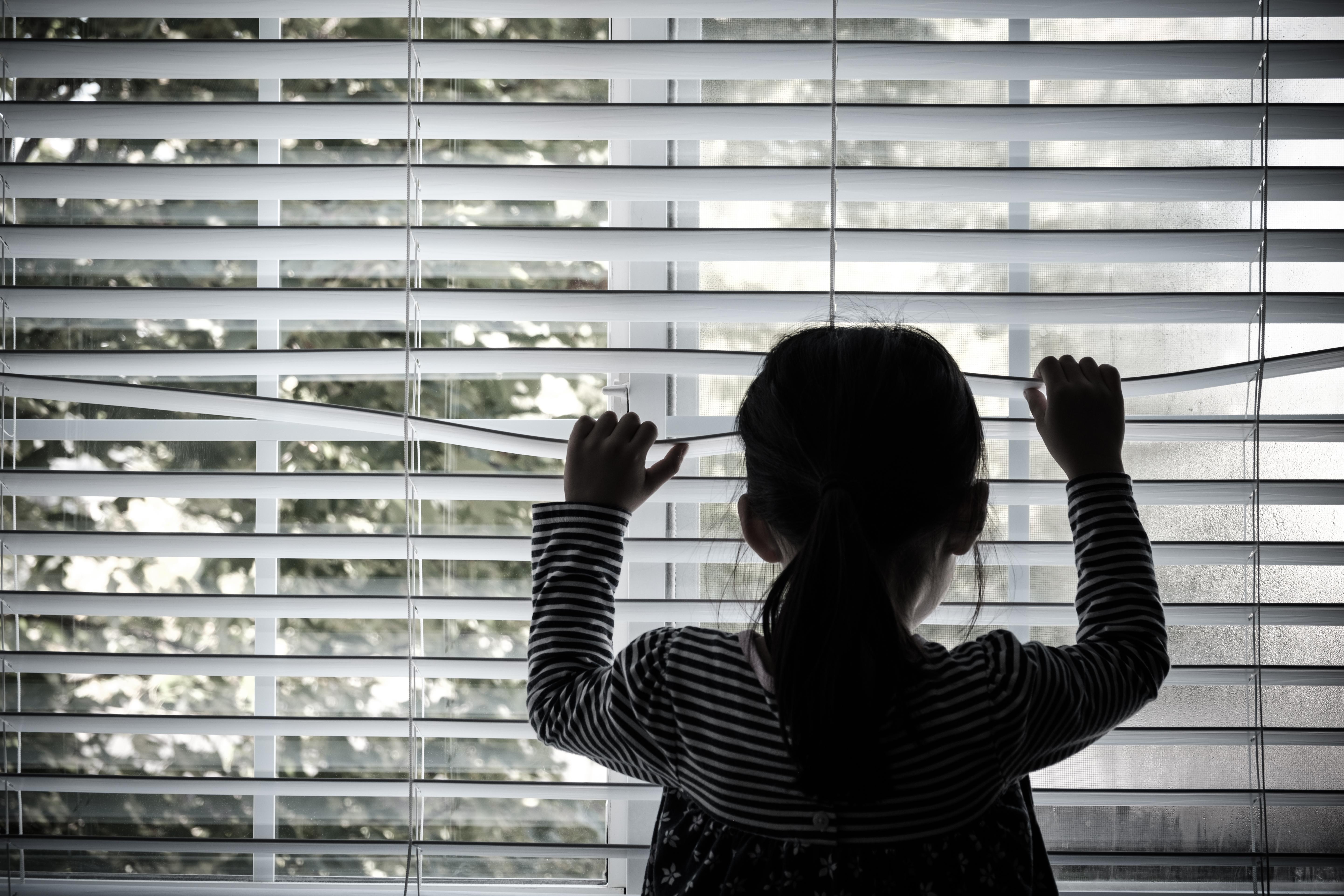 lonely-little-kid-in-front-of-a-window-5NT8QZE.jpg